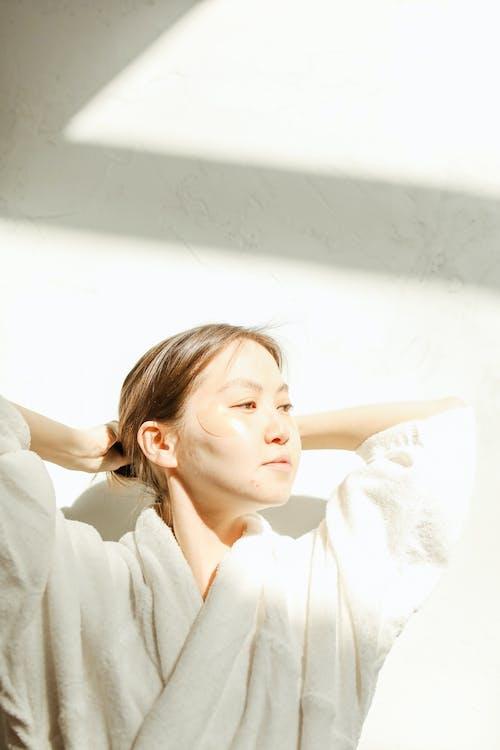 A Woman Wearing a Bathrobe and Under Eye Masks