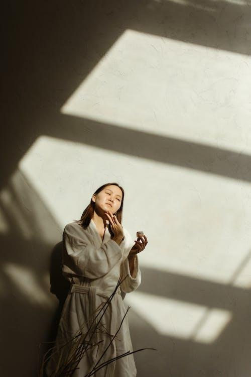 A Woman Wearing a Robe Applying Facial Cream