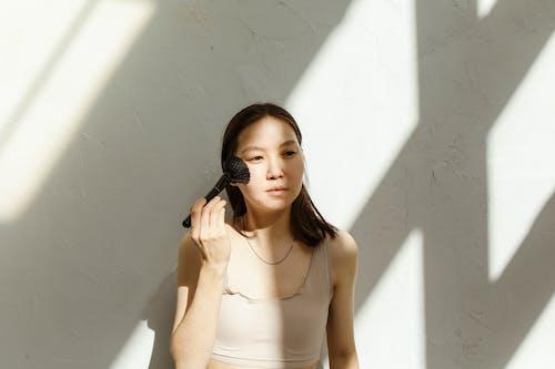 A Woman Using a Makeup Brush