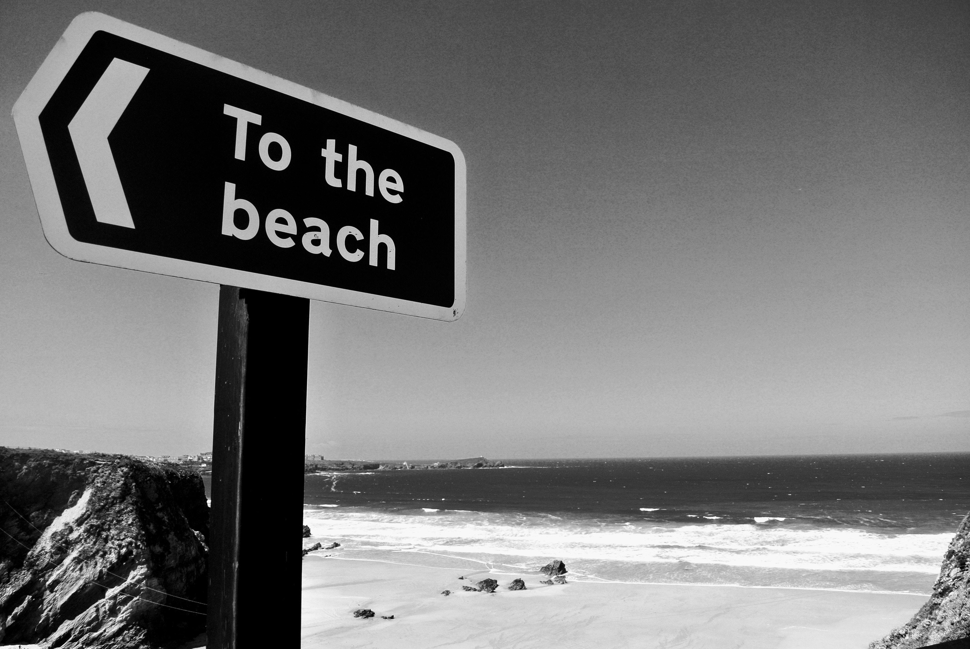 Grayscale Photo Of Beach Signage Free Stock Photo