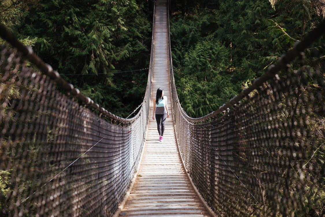 Woman Wearing Blue Sleeveless Shirt Walking on Bridge at Daytime