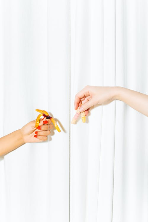 Hands Holding Gummy Worms