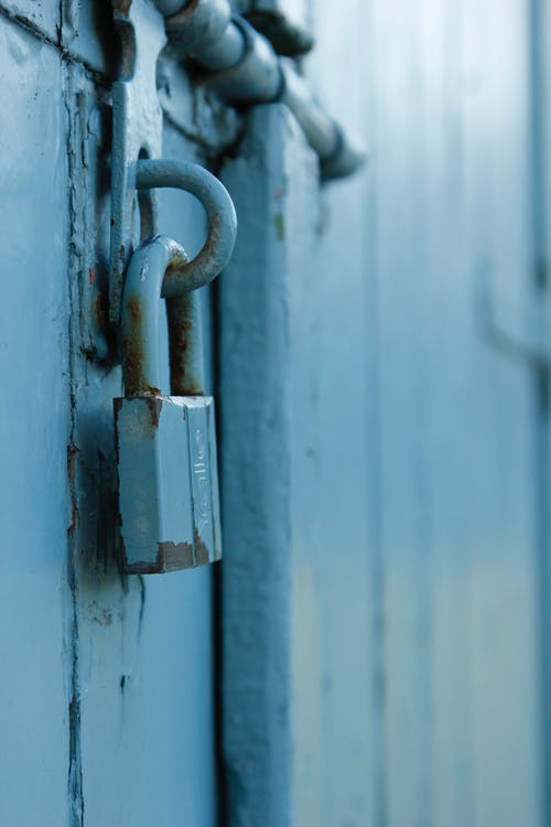 Gray Padlock on Blue Wooden Door