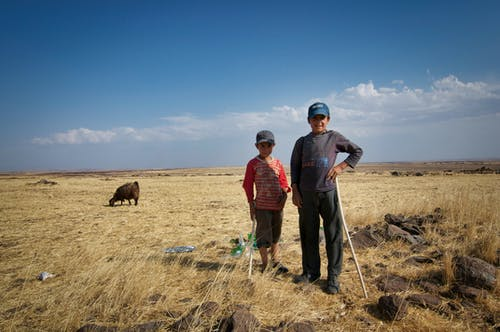 Ethnic herdsman with boy and wooden sticks standing on grass land behind grazing sheep under blue cloudy sky and looking at camera