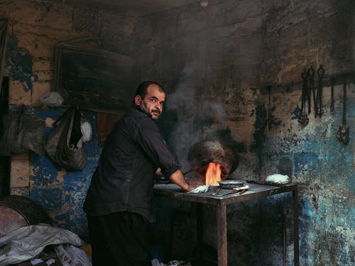 Back view of ethnic worker heating pot with burning flame while looking at camera in smithy