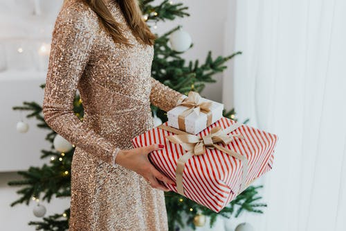 Woman in Golden Glittering Dress Holding Christmas Gifts