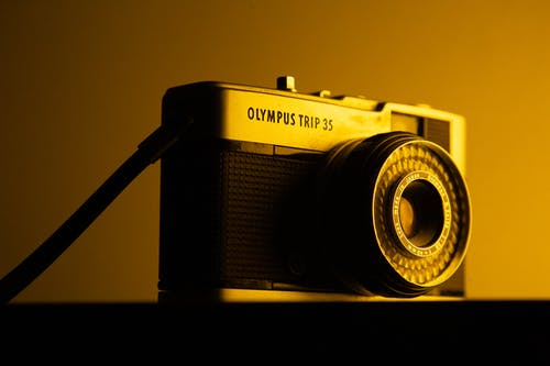 Low angle of old fashioned photo camera with strap and lens placed on table in dim light in studio inside