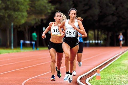 Fast athletes running on race track in stadium