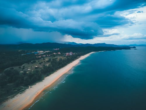 Aerial view of bright blue sea water washing sandy coastline with green trees under cloudy sky