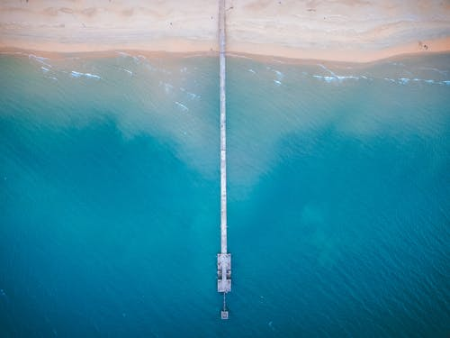 Empty beach and long pier on seaside