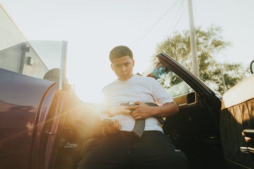 Man in White Crew Neck T-shirt Sitting on Car