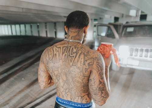 Man in Brown Long Sleeve Shirt With Tattoo on His Back