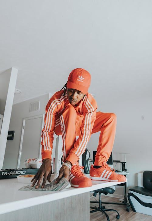 Man in Orange Jacket and Orange Helmet Sitting on Black Table
