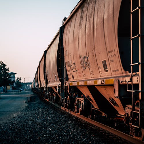 Large metal rusty train for carrying goods on railroad at station at daytime