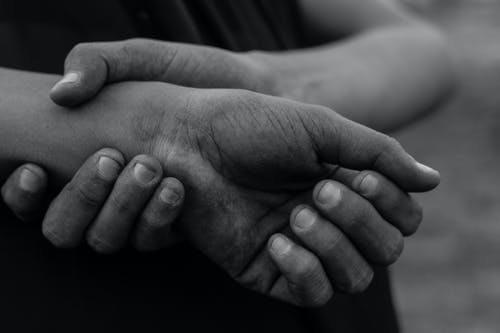 Grayscale Photo of Person Holding Babys Hand