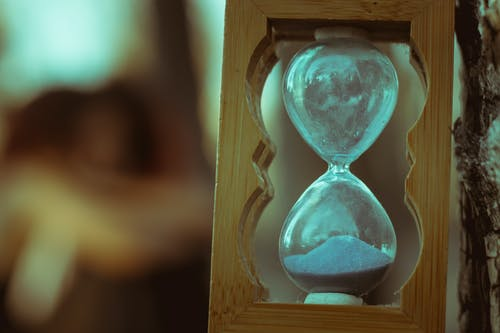 Glass bulbs of hourglass filled with sand framed in wood and placed in nature