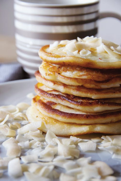 Delicious pile of pancakes served on white plate with shavings of white chocolate near mug on blurred background in light kitchen