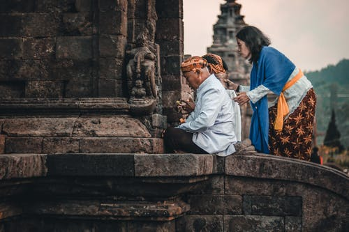 Side view of unrecognizable ethnic Buddhist male in traditional head wear praying near aged temple behind female with jug