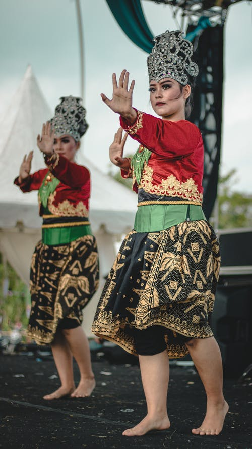 Young barefoot ethnic women in traditional costumes and crowns dancing on stage in concert