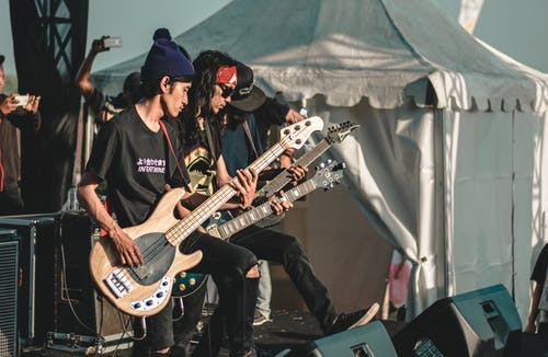 Male rock band guitarists performing live on outdoor stage