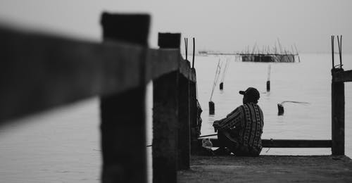 Black and white back view male in casual wear sitting on shabby wooden quay and looking at rippling sea