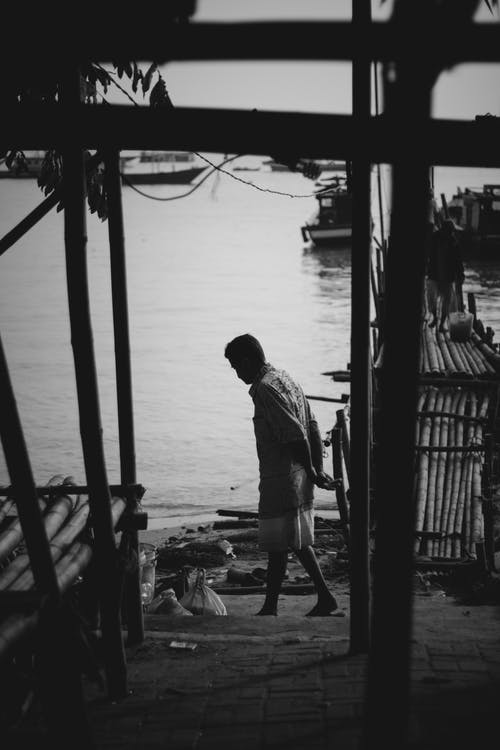 Anonymous man walking on waterfront of poor city