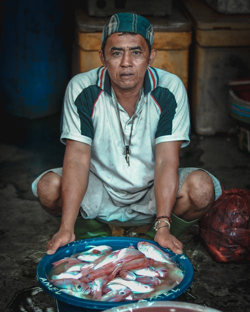 Full body Asian male in dirty clothes hunkering down near big plastic bowl of freshly caught fish in street market