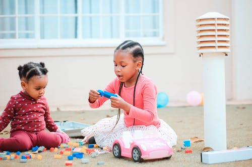 Cute little black girls playing with toys on floor