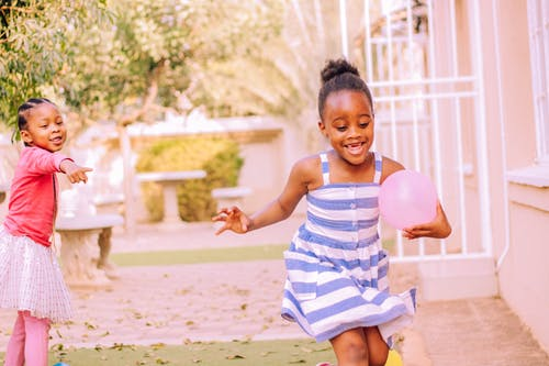 Happy little black children having fun in yard with balloons