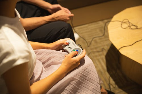 Unrecognizable couple playing video game with gamepads at home