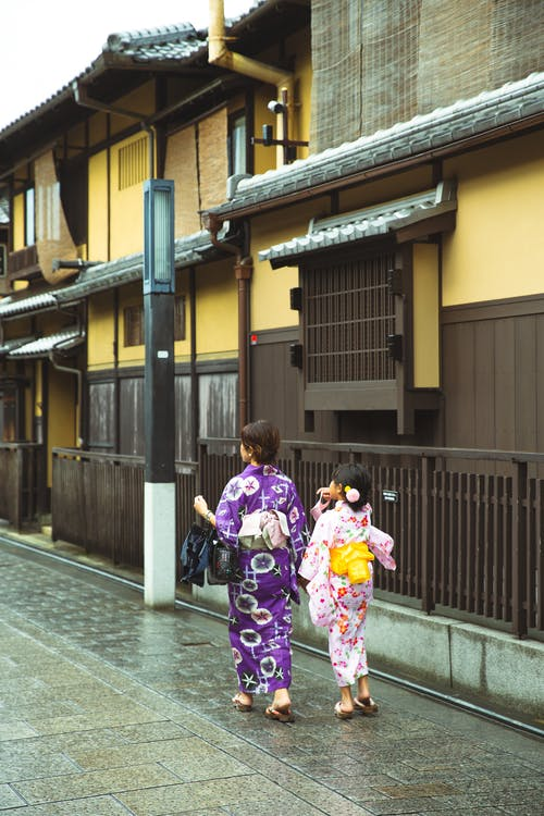 Back view of unrecognizable young Japanese female with little daughter in stylish traditional kimonos walking on street near aged buildings