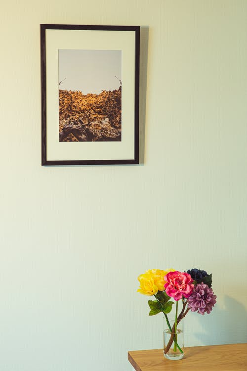 Colorful flowers in vase on wooden table placed near wall with framed photo