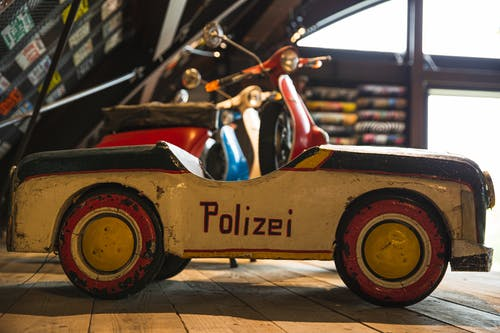Aged toy police car on wooden shelf