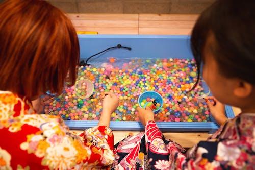 Crop unrecognizable girl washing fishbowl beads in basin