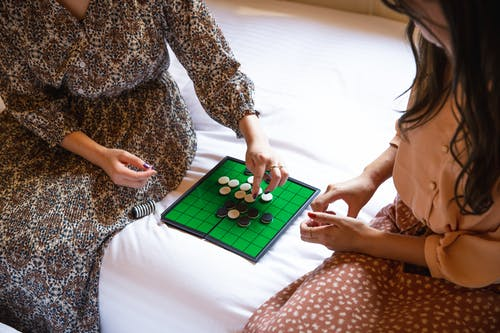 Crop unrecognizable women playing reversi game on bed