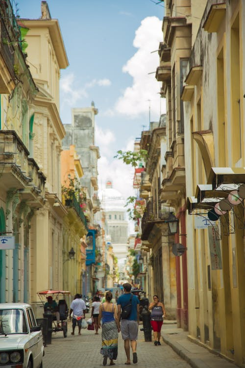 Tourists strolling on narrow pedestrian street between old classic buildings in historic district of Havana City on sunny summer day