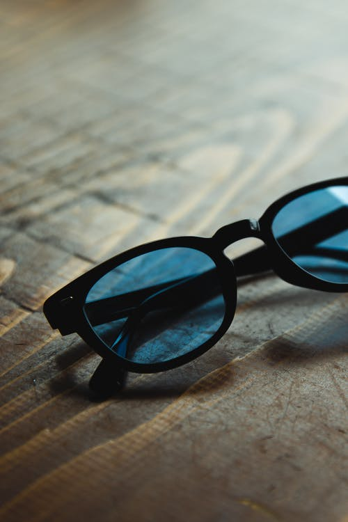 High angle trendy sunglasses with blue glass and black frames placed on wooden table