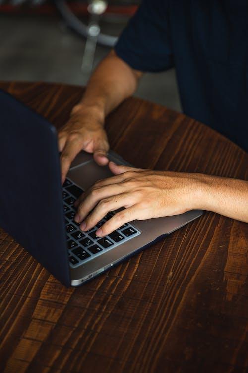 Crop unrecognizable man using contemporary laptop