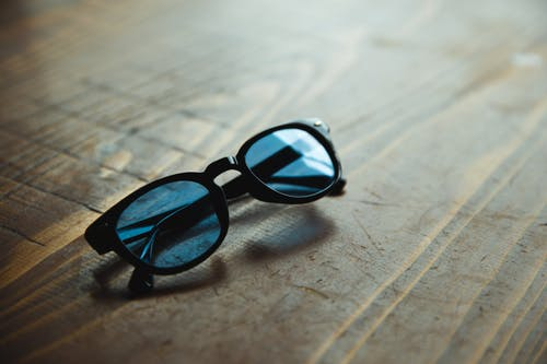 Stylish sunglasses with blue glass and black frames placed on shabby wooden table in daylight