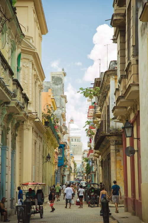 Crowded pedestrian street between old residential buildings in Havana Cuba on clear sunny weather