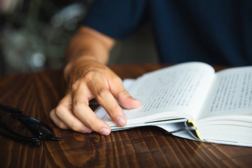 Crop unrecognizable man reading book at table