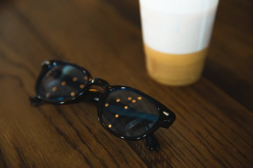 Trendy sunglasses placed on table near paper cup
