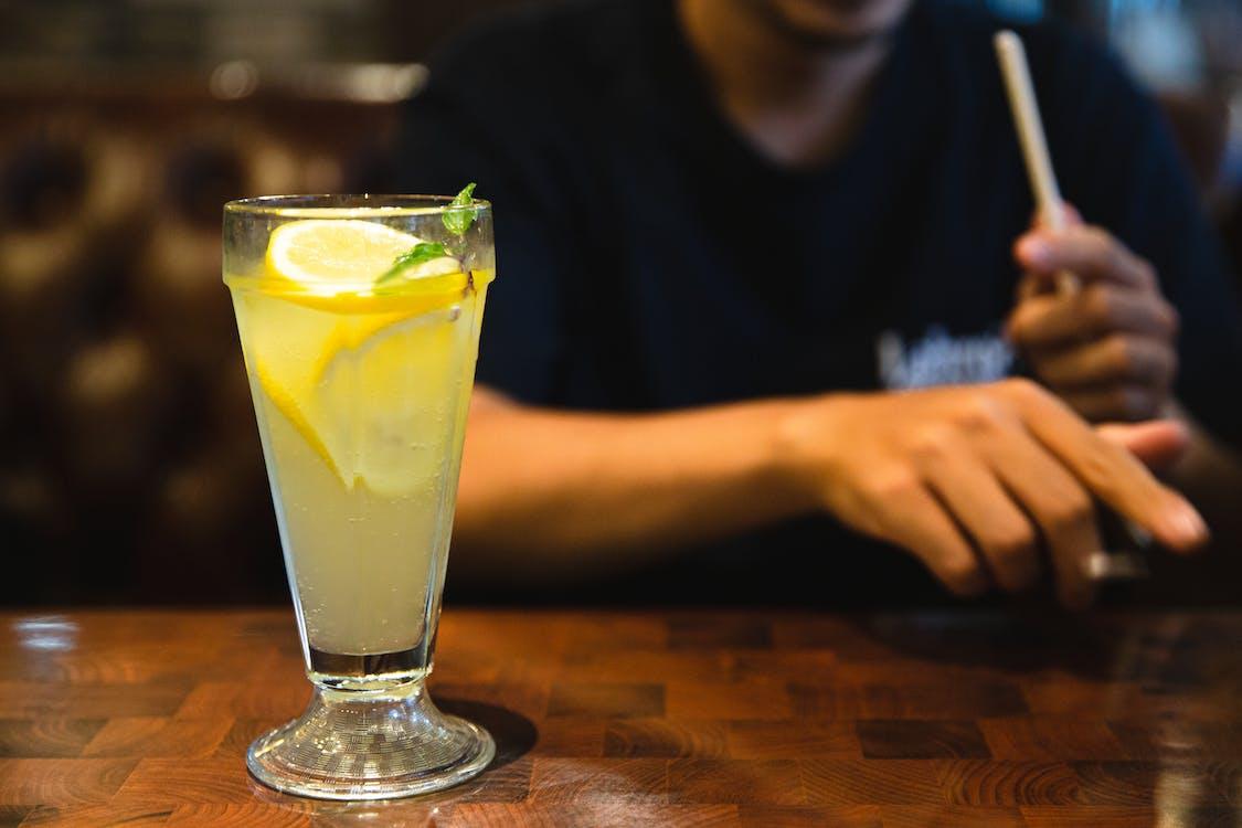 Crop faceless man sitting at table with fresh citrus lemonade