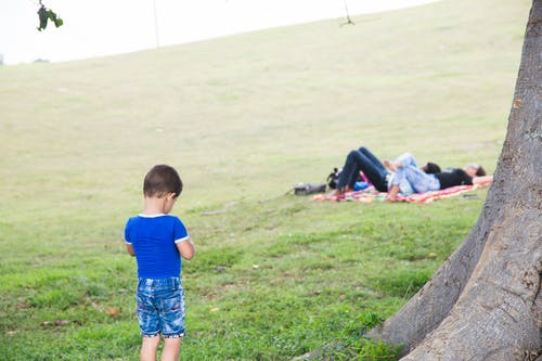 Unrecognizable boy on meadow against resting parents in summer