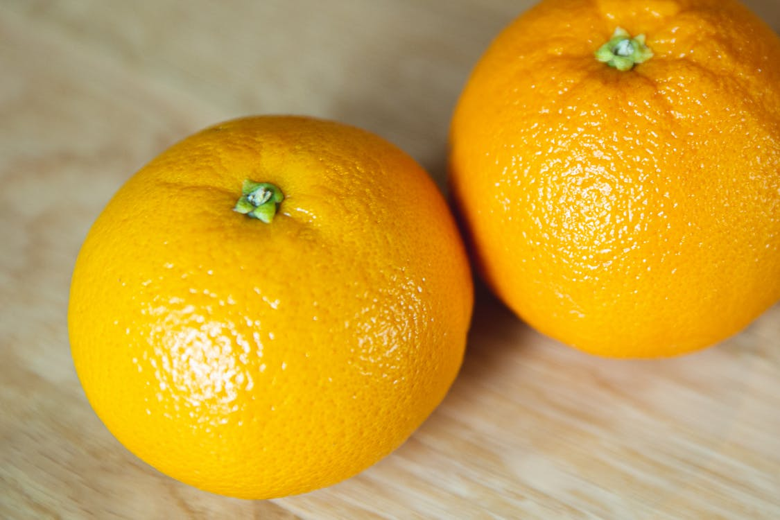 Bright whole ripe oranges on wooden table