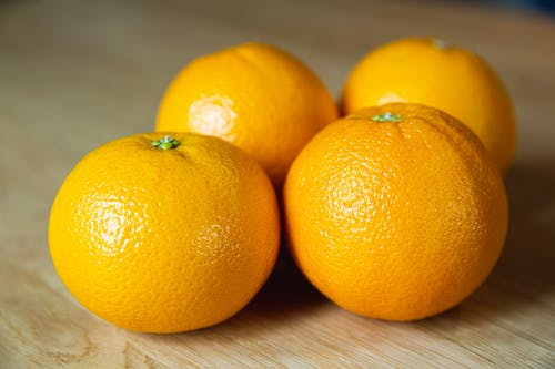Delicious similar sweet tangerines with bright peel and small pedicels on top in sunlight