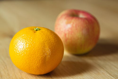 Ripe fresh tangerine with apple on table