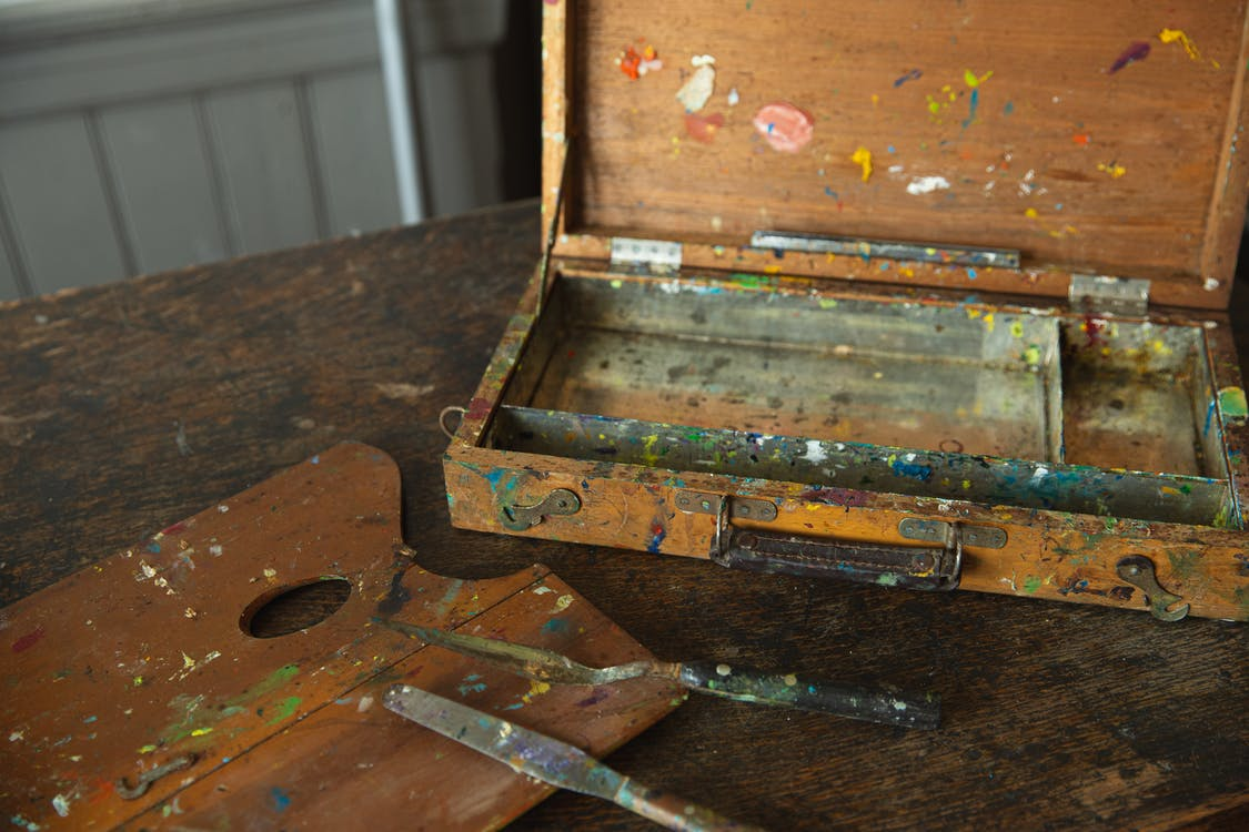 Aged wooden palette with spatulas on shabby table