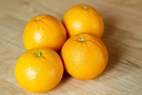 From above of yummy ripe sweet tangerines with colorful shiny peel on wooden table