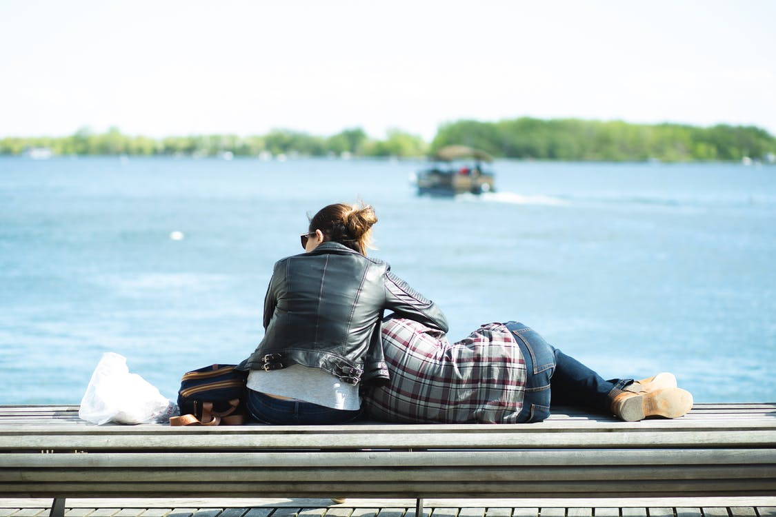 Back view of couple in casual clothes resting on wooden seafront against blue river in park